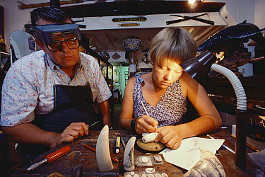 Young woman working on scrimshaw while proprietor of store oversees, Maui, Hawaii  -  Flip Nicklin