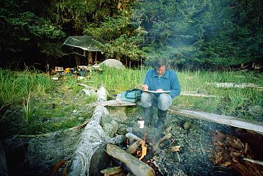 Humpback Whale (Megaptera novaeangliae) biologist examining data at campfire, Alaska  -  Flip Nicklin