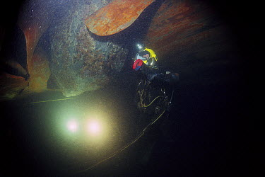 Diver examining boulder embedded in the hull of the sunken Exxon Valdez after oil spill, Prince William Sound, Alaska  -  Flip Nicklin