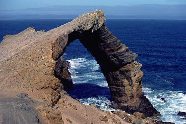 Waves seen through natural bridge in rock, Skeleton Coast, Namibia  -  Jim Brandenburg