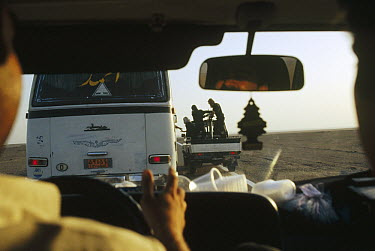 Researchers' military escort gets ice from bus while maintaining high speed, near the Afghan border, Iran  -  Mark Moffett