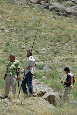 Researchers Bob Macey, Ted Papenfuss and Hadi Fahini with fishing poles hunting for specimens in desert, Deh Bala, Iran  -  Mark Moffett