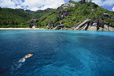 Swimmer and coral sand beaches with unique granite formations, Seychelles  -  Norbert Wu