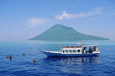 Nusantara Dive Center boat anchored at Bunaken Island dive site with Manado Tua Volcano in the distance, Manado, North Sulawesi, Indonesia  -  Fred Bavendam
