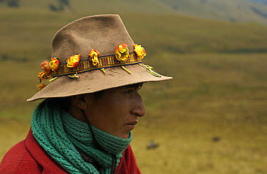Chagra cowboy portrait with roses in his hat band, on an overnight ride at a hacienda to herd cattle, Andes Mountains, Ecuador  -  Pete Oxford