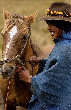 Chagra cowboy with Mountain roses in the band of his hat and his Horse at a hacienda during the annual overnight cattle round-up, Andes Mountains, Ecuador  -  Pete Oxford