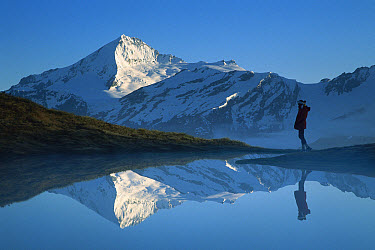 Mt Aspiring and hiker reflected in lake at dawn, Cascade Saddle, Mt Aspiring National Park, New Zealand  -  Colin Monteath/ Hedgehog House