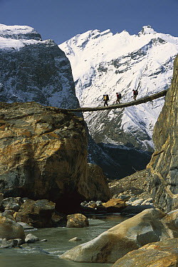 Trekkers cross a swing bridge over the Braldu River en route to Baltoro Glacier, Karakoram Mountains, Pakistan  -  Colin Monteath/ Hedgehog House