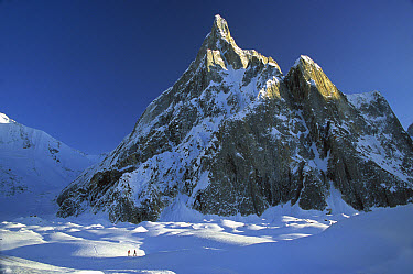 Skiers under rock spire, unnamed peak near Concordia, Baltoro Glacier, Karakoram Mountains, Pakistan  -  Colin Monteath/ Hedgehog House