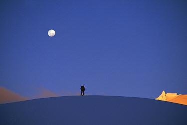 Ski-touring on Fox Glacier under moonrise at sunset, Westland National Park, New Zealand  -  Nick Groves/ Hedgehog House