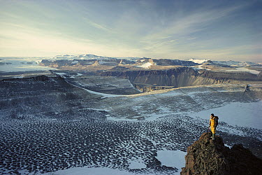 Man standing on a rock overlooking the Olympus Range, dry valleys, Antarctica  -  Colin Monteath/ Hedgehog House