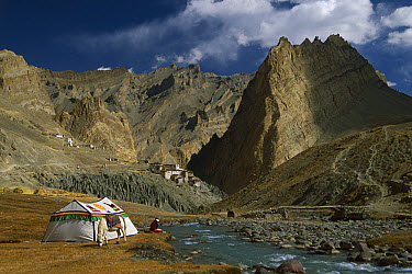 Trekker writes in diary beside Tibetan tent, Photoskar village, Ladakh, Himalayas, northwest India  -  Colin Monteath/ Hedgehog House