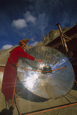 Monk boiling water with solar reflector, Lingshet Monastery, Ladakh, northwest India  -  Colin Monteath/ Hedgehog House