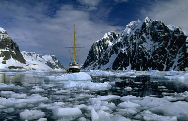 Sailboat avoiding broken ice, Mt Cloos of the Antarctic Peninsula on the left and Wandel Peak of Booth Island on the right, Lemaire Channel, Antarctica  -  Flip de Nooyer