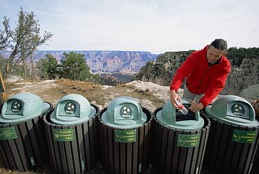 Tourist depositing plastic bottle into recycling garbage cans in parking lot, South Rim, Grand Canyon National Park, Arizona  -  Yva Momatiuk & John Eastcott