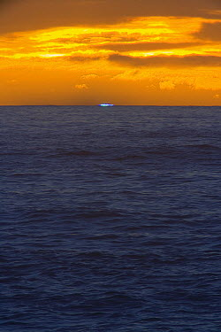 Blue Flash, rare optical phenomenon of refraction of light spectrum when air is clear, briefly visible on horizon of Pacific Ocean at sunset, winter, South Island, New Zealand  -  Yva Momatiuk & John Eastcott
