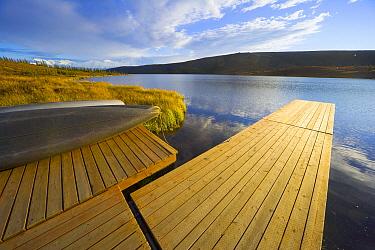 Small cumulus clouds cover blue sky above Wonder Lake, wooden canoe dock and snowy Mt.McKinley and other peaks in Alaska Range, fall evening, Denali National Park, Alaska  -  Yva Momatiuk & John Eastcott