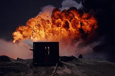 Spraying water on burning oil well from heat-shielding shed, Kuwait, post Gulf War  -  Ross Couper-Johnston/ npl
