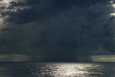 Rain and clouds over sunlit sea  -  Peter Scoones/ npl