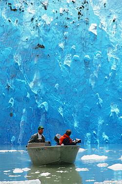 Small boat in water filming near blue iceberg, Alaska  -  Neil Lucas/ npl