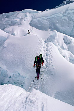 Climber crossing a crevasse, Khumbu Ice Fall, Mount Everest, Nepal  -  Doug Allan/ npl