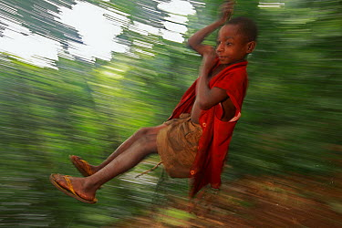 Baka child swinging on rope made from a single piece of bark, Cameroon  -  Cyril Ruoso