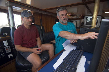 Blue Whale (Balaenoptera musculus) researchers, Bruce Mate at right, looking at tracking data, Costa Rica  -  Flip  Nicklin