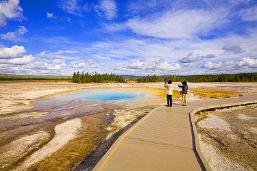 Tourists photgraphing Opal Pool, Midway Geyser Basin, Yellowstone National Park, Wyoming  -  Yva Momatiuk & John Eastcott