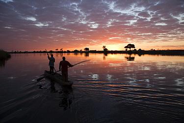 Fishermen in mokoro boat at sunrise, Chobe River, Namibia
