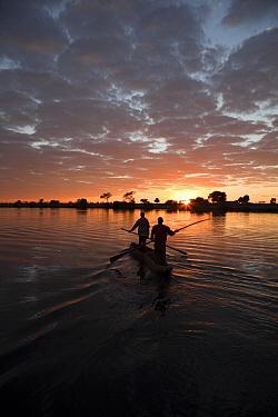 Fishermen in mokoro boat at sunrise, Chobe River, Namibia  -  Richard Du Toit
