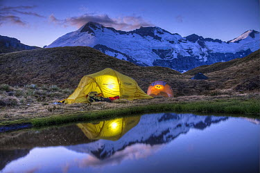 Campers read in tents lit by flashlight, Cascade Saddle, Mount Aspiring National Park, New Zealand  -  Colin Monteath/ Hedgehog House