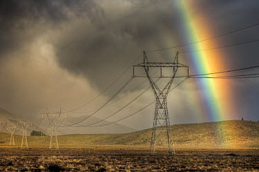 Powerlines, rainbow forms as evening sun lights up rain clouds, Canterbury, New Zealand  -  Colin Monteath/ Hedgehog House