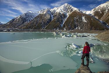 Woman overlooks frozen lake, Tasman Glacier, Mount Cook National Park, New Zealand  -  Colin Monteath/ Hedgehog House