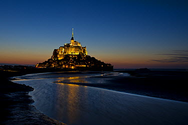 Mont Saint-Michel at sunset with water in surrounding bay, Normandy, France  -  Jim Brandenburg