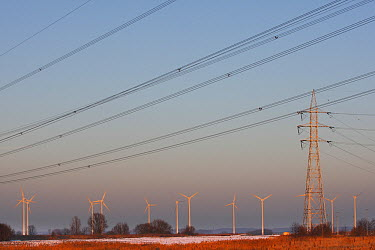 Windmills at sunset with powerlines, Rechteroever, Belgium  -  Wouter Pattyn/ Buiten-beeld