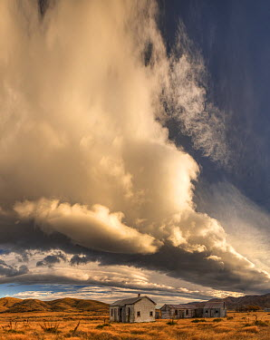 Cloud build up over historic farm buildings near Saint Bathans, Central Otago, New Zealand  -  Colin Monteath/ Hedgehog House