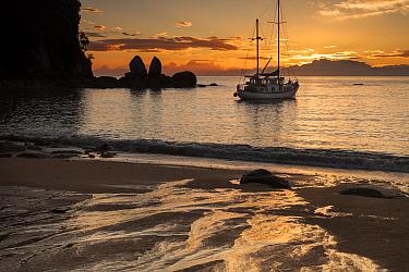 Sailboat anchored in bay at sunrise, Split Apple Rock, Abel Tasman National Park, South Island, New Zealand  -  Colin Monteath/ Hedgehog House
