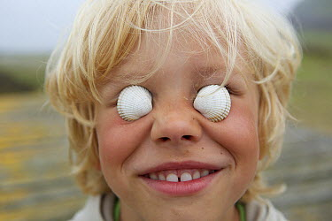 Common Cockle (Cerastoderma edule) shells on boy's eyes, France  -  Luc Hoogenstein/ Buiten-beeld