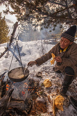 Tsataan man making tea in taiga forest while bread cooks beside the open fire during spring Reindeer round up, Mongolia  -  Colin Monteath/ Hedgehog House