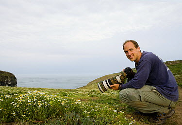 Sebastian Kennerknecht photographing on coast, Skomer Island National Nature Reserve, Skomer Island, Pembrokeshire, Wales, United Kingdom  -  Sebastian Kennerknecht