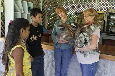 Brown-throated Three-toed Sloth (Bradypus variegatus) conservationist, Judy Avey-Arroyo, and biologist, Rebecca Cliffe, teaching local children about sloths, Aviarios Sloth Sanctuary, Costa Rica  -  Suzi Eszterhas