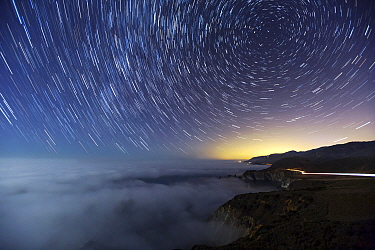 Star trails, fog and car lights at night along the Pacific coast, Big Sur, California