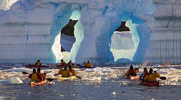 Kayakers approaching arches in iceberg, Cierva Cove, Antarctic Peninsula, Antarctica