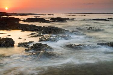 Sunrise over coastal rocks, Salalah, Oman