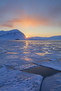 Midnight sun over ice floes in late winter, Svalbard, Spitsbergen, Norway