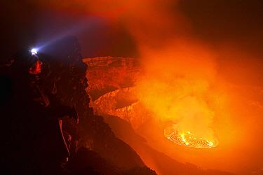 Man looking into crater at night, Mount Nyiragongo, Virunga National Park, Democratic Republic of the Congo