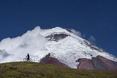 Cyclist near snow-covered peak, Cotopaxi Volcano, Cotopaxi National Park, Andes, Ecuador