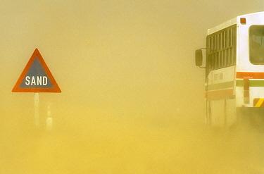 Road sign and bus during sandstorm, Namib Desert, Namibia