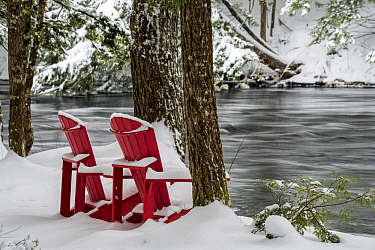 Adirondack chairs along river in winter, Mersey River, Kejimkujik National Park, Nova Scotia, Canada