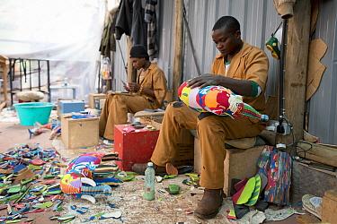 Artists working on sculptures made from reclaimed flip-flops, Ocean Sole, Nairobi, Kenya